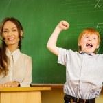 Little happy redhead boy answering near blackboard in school — Stock Photo