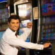 Handsome happy brunette man in white shirt near slot machine  — Stock Photo