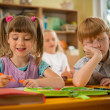 Little girl in school with sleepy redhead classmate — Stock Photo #36578015