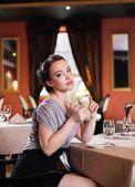 Vacker ung flicka med fika ensam i en restaurang — Stockfoto