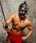 Gladiator with muscular body with sword and helmet — Stock Photo