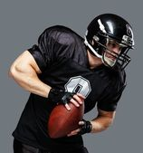 American football player with ball wearing helmet and jersey — Стоковое фото