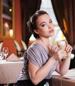 Beautiful young girl with cup of coffee alone in a restaurant — Stock Photo