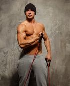 Handsome man with muscular body doing fitness exercise — Stock Photo