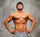 Handsome man with muscular torso in beanie hat posing — Stock Photo