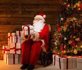 Santa Claus sitting on rocking chair in wooden home interior presenting gift box — Stock Photo