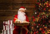 Jultomten i trä heminredning sitter bakom bordet och skriva brev med gåspenna penna — Stockfoto