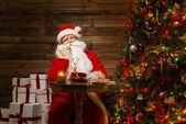 Santa Claus with phone in wooden home interior — Stock Photo