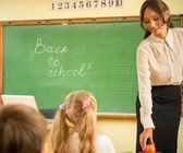 Beautiful young woman teacher in front a class — Stock Photo