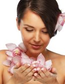 Beautiful dreaming young brunette woman with orchid flowers — Stock Photo