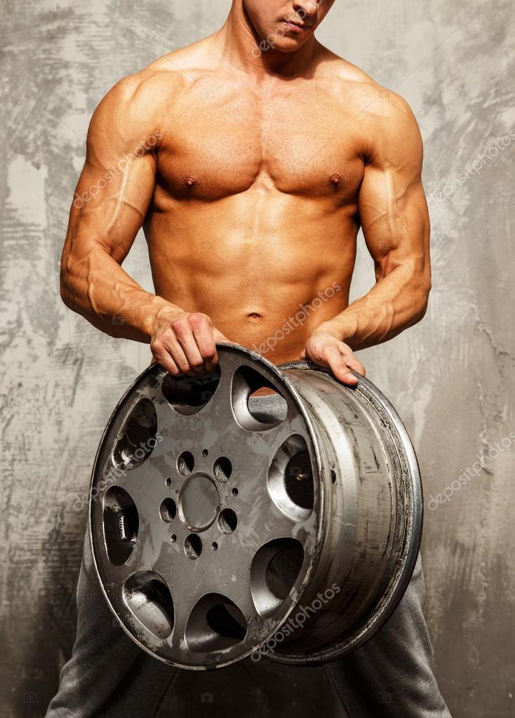 Schöner sportlicher Mann mit muskulösen Körper halten