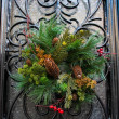 Christmas wreath with cones hanging on a door — Stock Photo