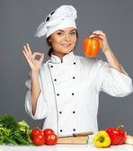 Beautiful young woman holding fresh paprika — Stock Photo