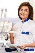 年轻的黑发女人牙医与牙科工具在牙医的手术治疗 — 图库照片