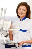Young brunette woman dentist with dental tools in dentist's surgery — Foto de Stock