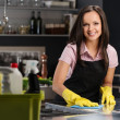 Beautiful cheerful brunette woman in gloves cleaning modern kitchen — Stockfoto