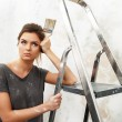 Disgruntled young brunette woman with ladder and painting brush — Stock Photo #37395837