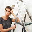 Stock Photo: Disgruntled young brunette womwith ladder and painting brush