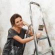 Happy beautiful young woman doing wall painting — Stock Photo #37395847