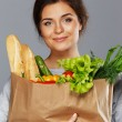 Smiling young brunette woman with grocery bag full of fresh vegetables — Stock Photo