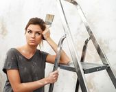 Disgruntled young brunette woman with ladder and painting brush — Stock Photo