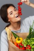 Smiling brunette woman with grocery bag full of fresh vegetables and cherry tomatoes — Stock Photo