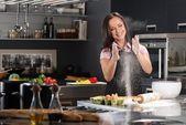 Ung kvinna att ha kul med mjöl medan degen på ett modernt kök — Stockfoto