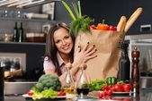 Young woman with grocery bag full of fresh vegetables on a modern kitchen — Stock Photo