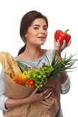 Smiling brunette woman with grocery bag full of fresh vegetables and red paprika — Stock Photo