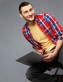 Stylish young man with a laptop — Stock Photo