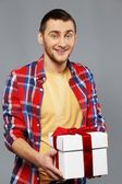 Stylish young man in shirt and beanie hat with gift box — ストック写真