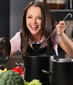 Cheerful young woman in apron on modern kitchen will ladle tasting from pot — Stock Photo