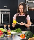 Cheerful young woman in apron on modern kitchen cutting vegetables — Stock Photo