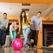 Group of four young smiling people playing bowling — Stock Photo #38757363