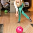 Young smiling blond woman throwing ball in a bowling club — Stock Photo