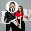 Beautiful smiling couple holding word LOVE made from foam plastic — Stock Photo #38757633