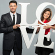 Beautiful smiling couple holding word LOVE made from foam plastic — Stock Photo