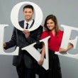 Beautiful smiling couple holding word LOVE made from foam plastic — Stock Photo #38757661