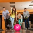 Group of four young smiling people playing bowling — Zdjęcie stockowe #38757809