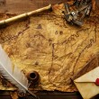 Sextant, spyglass and envelope on vintage map over wooden background — Stock Photo