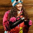 Happy womin ski wear with thermos against wooden wall — Stock Photo #38757919