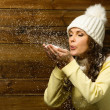 Beautiful woman in knit hat blowing snow from her hands — Stock Photo #38757925