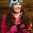 Happy womin ski wear with cup of hot drink against wooden wall — Stock Photo #38757927