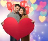 Happy couple holding handmade paper heart and red balloons over bokeh background — Stock Photo