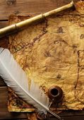 Spyglass and quill pen on old map over wooden background — Stock Photo