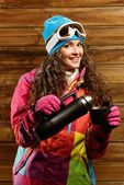 Happy woman in ski wear with thermos against wooden wall — Stock Photo