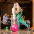 People watching young blond woman throwing bowling ball — Stock Photo