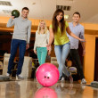 Group of four young smiling people playing bowling — Stockfoto #39147387