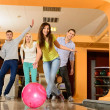 Group of four young smiling people playing bowling — Stock Photo #39147423