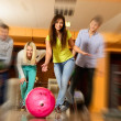 Group of four young smiling people playing bowling — Stockfoto #39147425